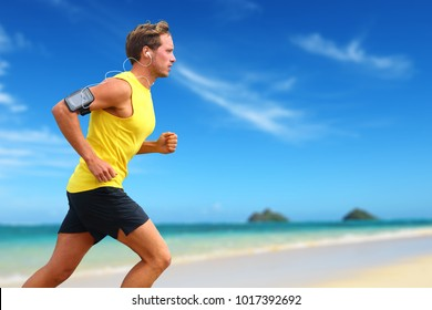 Runner listening smartphone music running on beach. Lanikai, Oahu, Hawaii, USA. Male athlete jogging on ocean beach or waterfront working out with smart phone app device and earphones in summer.