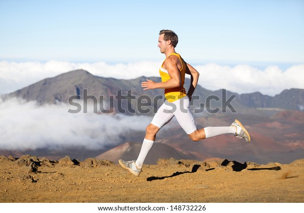 Runner man athlete running sprinting fast. Male sport fitness model training a sprint in amazing nature landscape outdoors at speed wearing sporty runners clothing compression socks. Strong fit man