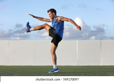 Runner man getting ready to run doing warm-up dynamic leg stretch exercises routine, Male athlete stretching lower body hamstring muscles before going running outside in summer outdoors.