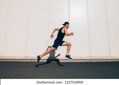 Runner man running fast in industrial city background. Sport, athletics, fitness, jogging activity