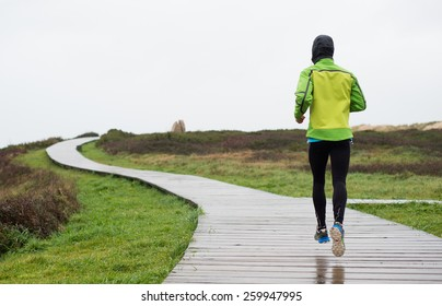 Runner man running in a rainy day. Man is running on a boardwalk