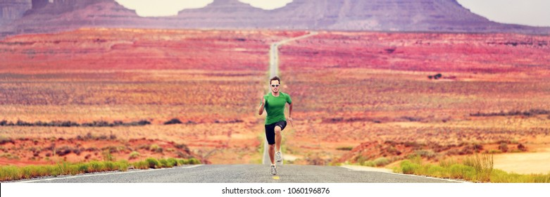 Runner man running sprinting on road of mountain nature. Male sprinter training for success. Fit sports athlete working out in amazing desert landscape. Panorama banner with copy space on background.
