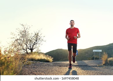 Runner. A man in sports outfit runs along the mountain trail.