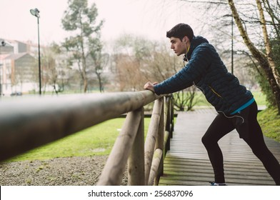 Runner man stretching in a park outdoors in a rainy day
