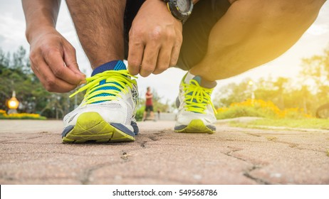 Runner man tying running shoes laces getting ready for race on road.