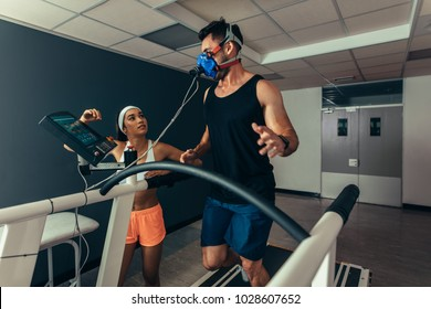 Runner with mask on treadmill in laboratory with woman standing by. Woman monitoring runner with mask on treadmill in laboratory