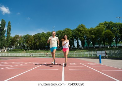Runner on competition and future success. Couple running on arena track. Coach and trainer at workout. Man and woman sunny outdoor on blue sky. Sport and healthy fitness.