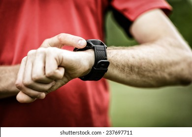 Runner on mountain trail looking at smartwatch or sport watch, checking gps navigation position map or heart rate pulse trace, using heart monitor equipment. Sport and fitness outdoors in nature.
