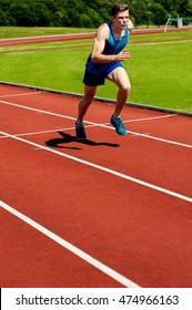 Runner practicing in athletics stadium racetrack.