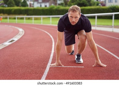 Runner ready on the starting grid on a race track for the start of a race looking up at the camera with a look of focused determination, conceptual image with copy space