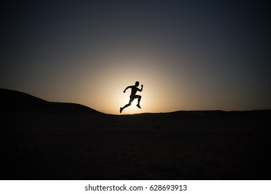runner. silhouette of running man on sunset fiery sky background in mountain, sport and recreation, future and success, people and nature, speed and healthy lifestyle