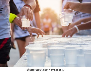 Runner take a water in a marathon race with sunrise
