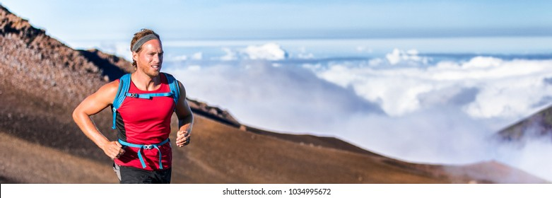 Runner trail running fitness man on endurance run - motivation and concentration on race in sky and clouds background on nature landscape. athlete wearing backpack training cardio.