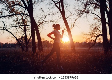 Runner training in autumn park. Woman running with water bottle at sunset. Active lifestyle. Healthcare