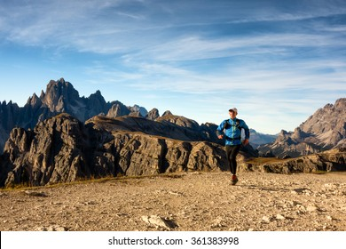 runner training on workout in the mountains near tre cime di lavaredo with peaks view