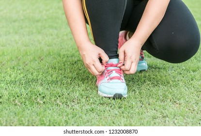Runner is tying up her shoelaces on the grass.Prepare Before Exercise