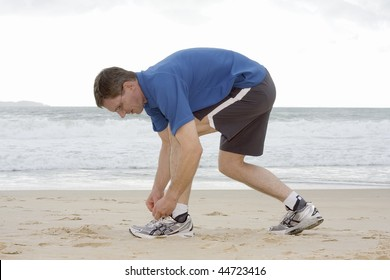 Runner tying his shoes on a beach