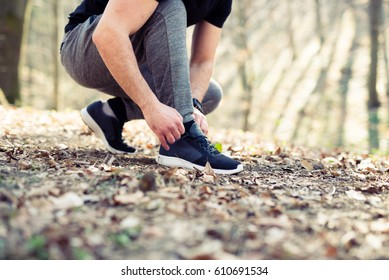 Runner tying his shoes preparing for a jog,grass