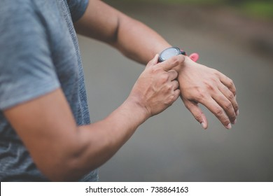 Runner using heart rate monitor training running, smartwatch checking performance or GPS. Man athlete looking at stopwatch. Healthy runner on running trail.