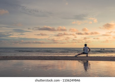 Runner warm up before run on the beach with reflection on the water, beautiful sky at sunset.