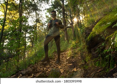 Runner wearing mask runs through autumn forest in the morning during sunrise