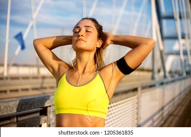 Runner woman doing stretching exercises at sunset in a bridge