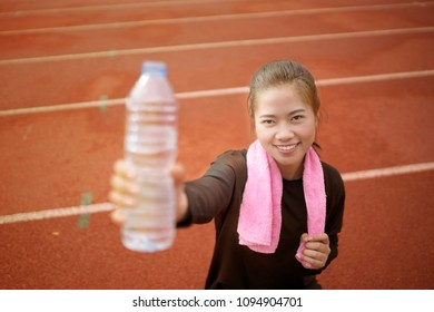 runner woman drinking water while exercises on the training at stadium