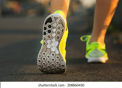 Runner woman feet running on road closeup on shoe. Female fitness model sunrise jog workout. Sports healthy lifestyle concept.