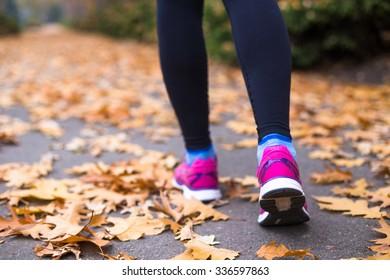 Runner woman feet running on autumn road closeup on shoe.