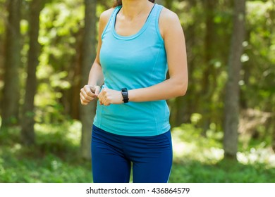 Runner woman with heart rate monitor running in forest.