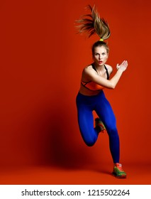 Runner woman isolated. Running fit fitness sport model with long hair in pony tail in blue Pants Gym  Stretch Sportswear, jogging  on red background.  Dynamic movement. Sport and healthy lifestyle.