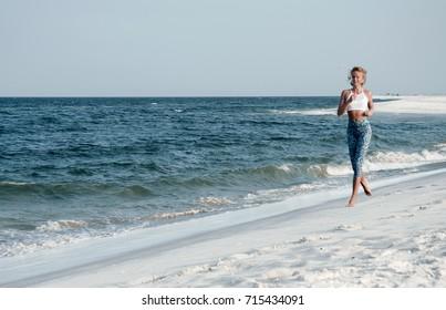 Runner woman running in the beach at sunset. Athletic fitness woman running on the beach. Outdoor workout.