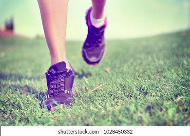 Runner woman runnning shoes jogging on park grass. Summer exercise active and healthy lifestyle.