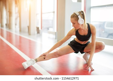 runner woman stretching leg muscle preparing for run on track. Female athlete doing legs stretches getting ready for cardio warmup