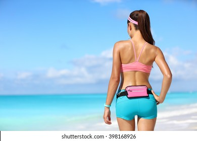 Runner woman taking a break from run with phone holder for music listening and fitness smart watch for activity tracker. View from back in sportswear. Wearable tech concept.