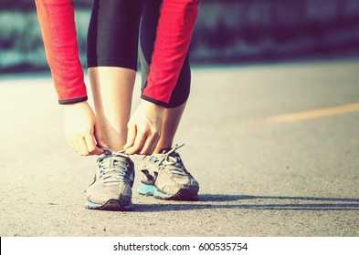 Runner woman tying laces on her old running shoes