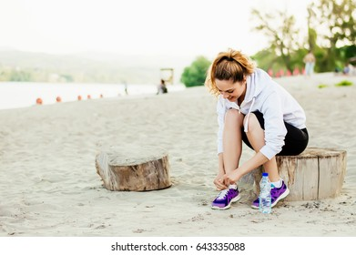 Runner woman tying laces of running shoes preparing for beach jogging.
