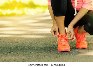 Runner woman tying up laces of shoes, getting ready run for cardio and weight loss, no face. Sportive wear in trend colors - vibrant coral neon color, positive  lifestyle for motivation concept banner