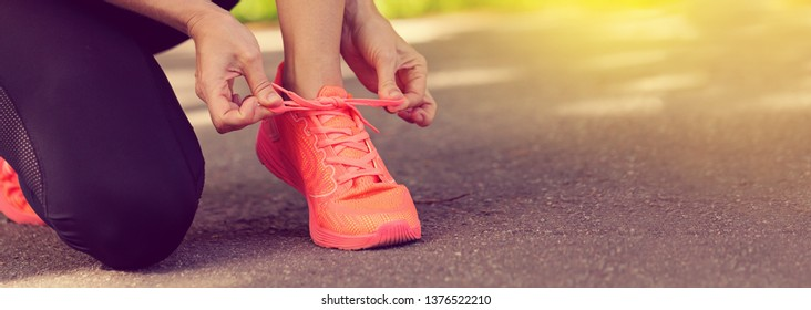 Runner woman tying up laces of shoes, getting ready to run for cardio and weight loss, no face. Sportive wear in trend colors - vibrant coral neon color, long crop banner