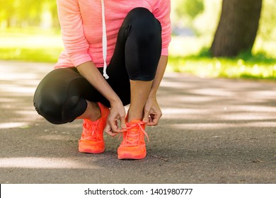 Runner woman tying up laces of shoes, getting ready to run for cardio and weight loss, no face. Sportive wear in trend colors - vibrant neon color, positive healthy lifestyle for motivation concept