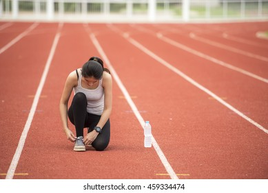 Runner woman tying running shoes laces getting ready for race on