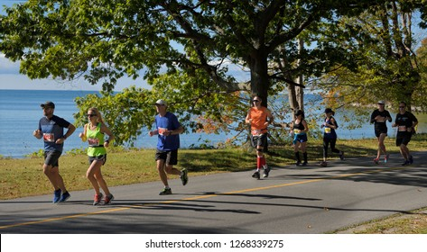 Runners in the 14th Annual County Marathon Prince Edward County on county road 12 Athol Bay, Lake Ontario in Sandbanks Provincial Park, Canada - September 30, 2017