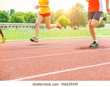 Runners athletes speeding in a athletic running track - Young people training outdoor for challenge competition - Close up on legs with back lighting - Warm filter with focus on right man ground foot