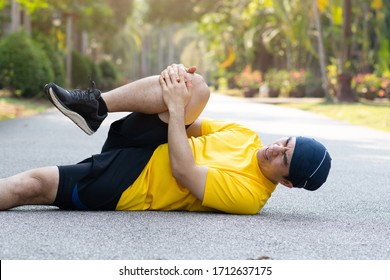 Runners catch the knee from accident on road in public park. Injury from run. Collapsed with pain, Sport and health care concept.