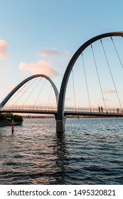 Runners crossing Elizabeth Quay Bridge in early morning light. The bridge is open to pedestrians and cyclists and is an iconic architectural feature of the quay. PERTH, WESTERN AUSTRALIA. AUGUST 2019.