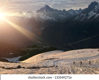 Runners descend a snow covered Alpine mountainside as the sun rises over the mountain landscape