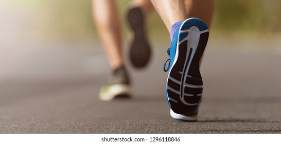 Runners feet running on road close up on shoe, male triathlete runner