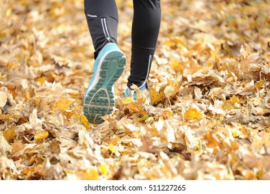 Runner's foots close-up on autumn walk in nature outdoors. healthy lifestyle and sport concepts.