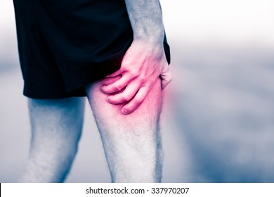 Runners leg pain on workout. Man holding sore and painful leg muscle, sprain or cramp ache filled with red pink bright place. Over trained injured person when exercising or running outdoors.