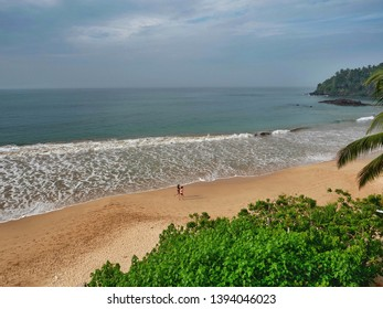 Runners on the beach in Mirissa. View from the Paradise Beach Club Hotel. Sri Lanka, March 16, 2019